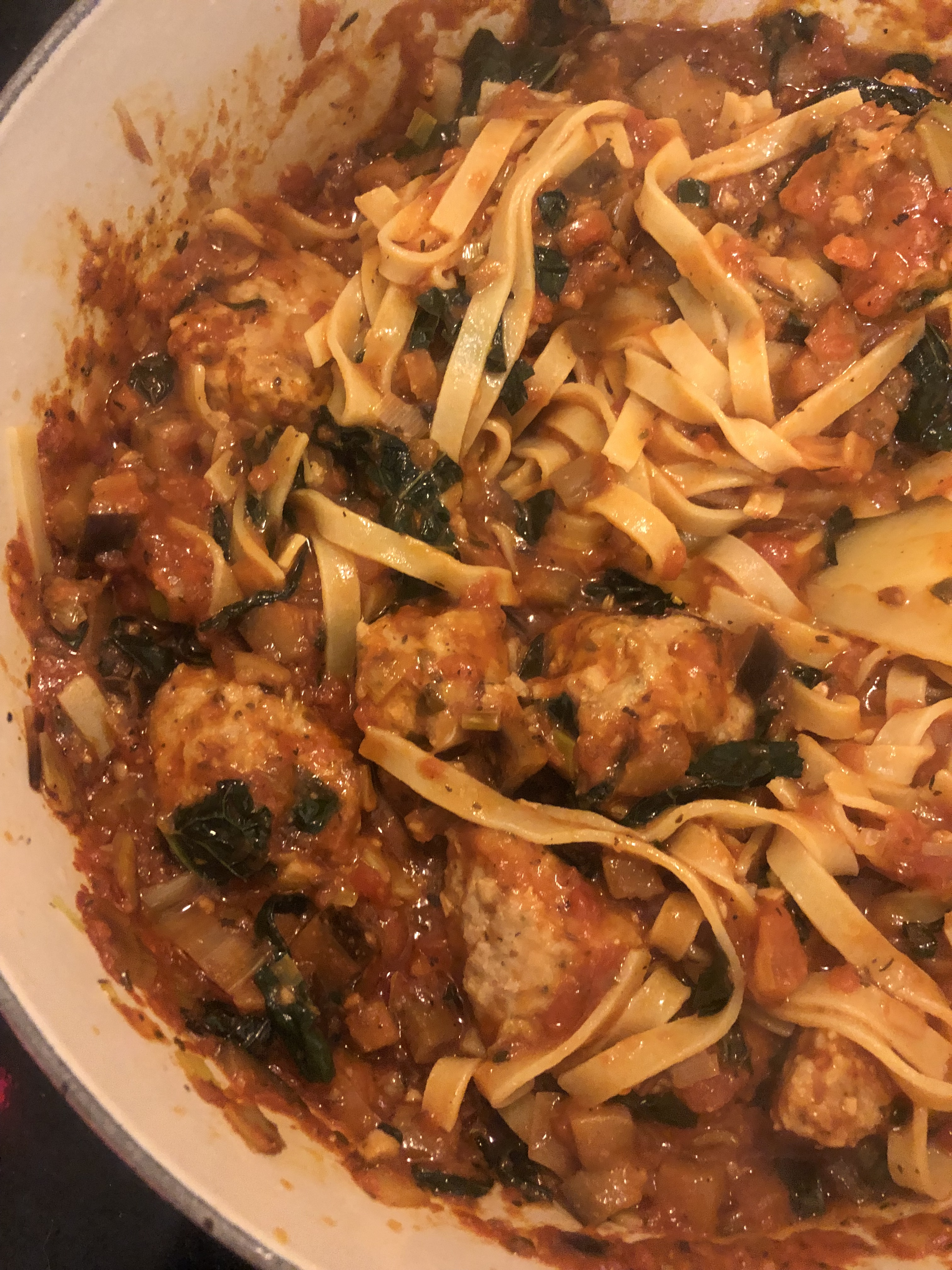 Chicken Meatballs with Eggplant, Leek and Kale Ragu over Almond Flour Fettuccine in a pot on the stove