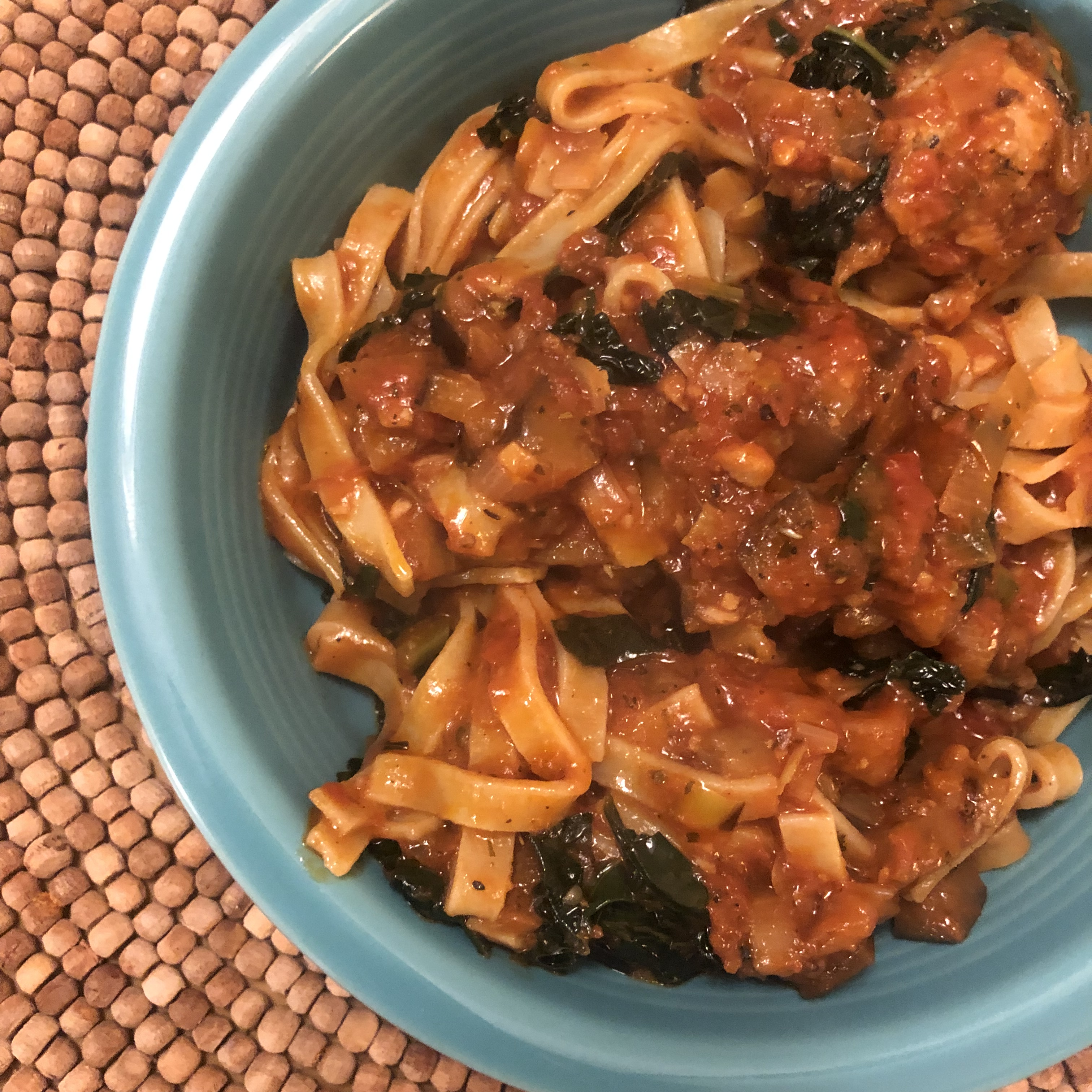 Chicken Meatballs with Eggplant, Leek and Kale Ragu over Almond Flour Fettuccine in a blue bowl.