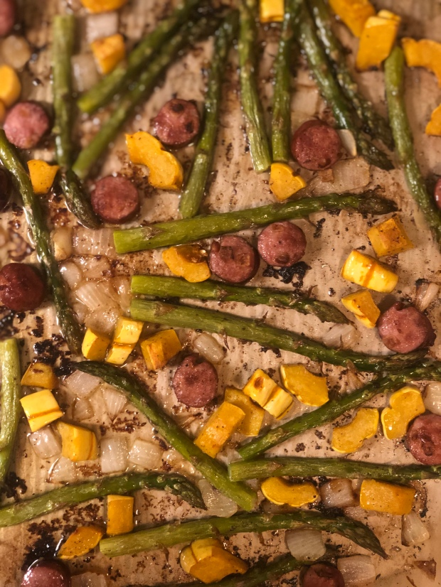 Sheet pan of roasted asparagus, delicate squash, onion and sausage fresh out of the oven