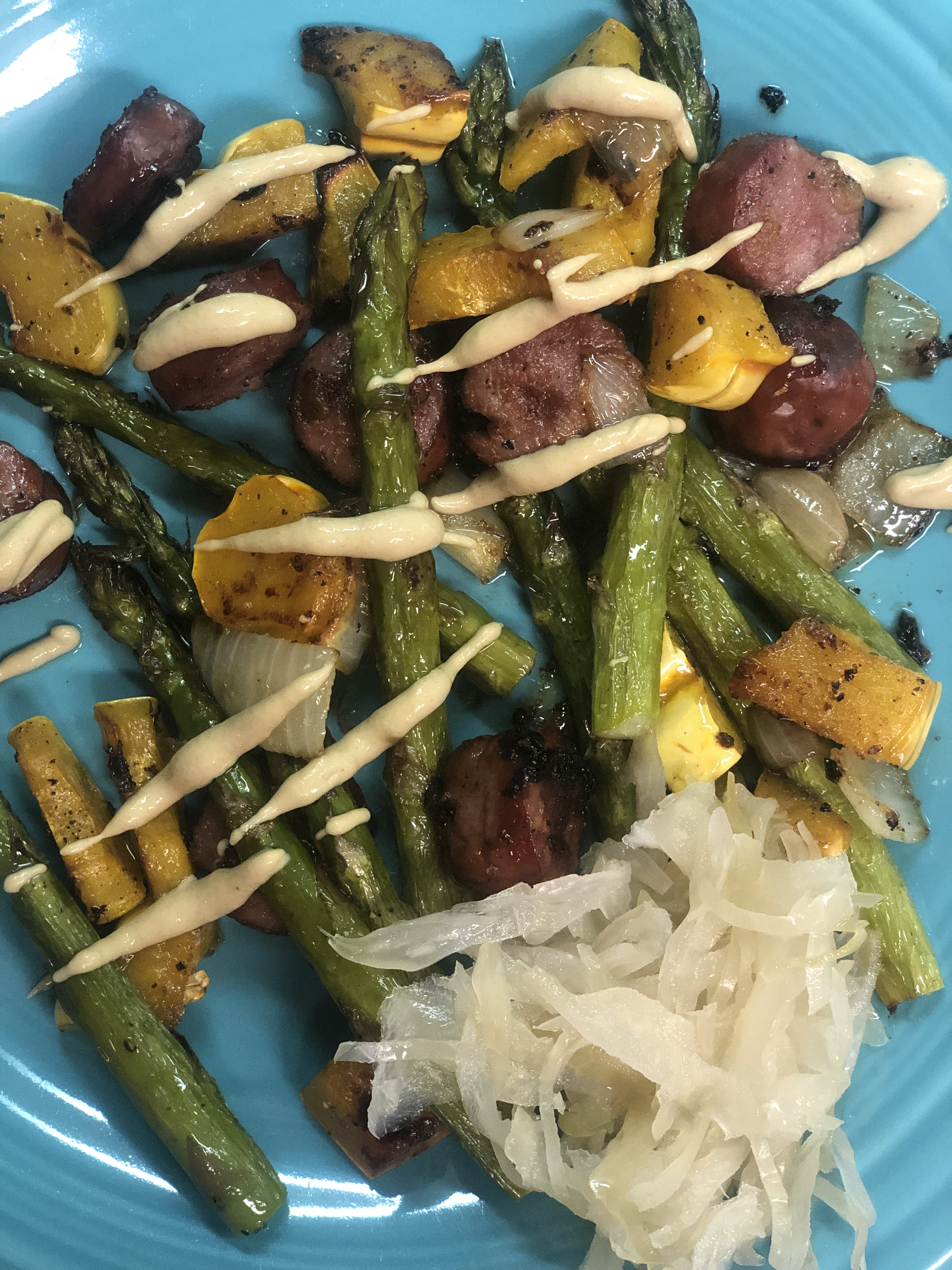 Roasted sausage, asparagus, delicata squash and onion with kraut and Dijon mustard on a blue plate